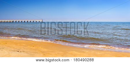 Warm summer day on sandy beach by Baltic sea in Lithuanian resort Palanga. Pedestrian pier extends into the sea. Tidal waves wash the sandy beach