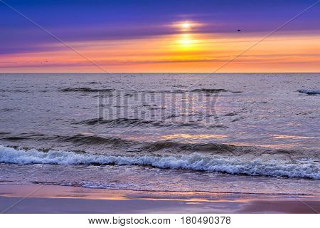 Sunset at Baltic sea in resort of Lithuania Palanga. Rays of sun shine through the low rare cirrus clouds. Tidal waves wash the sandy beach. Warm summer august evening on sea