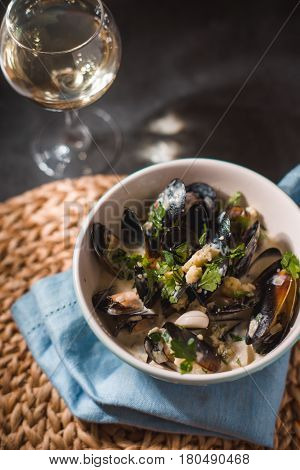 Mussels in sashes in sauce in a bowl on a napkin vertical