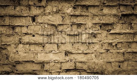Broken and worn down brick wall by weather conditions