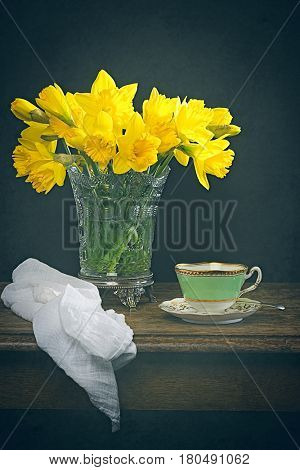 Spring daffodils still life with antique cup and saucer