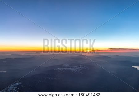 Snowy aegean mountains with mist during sunset