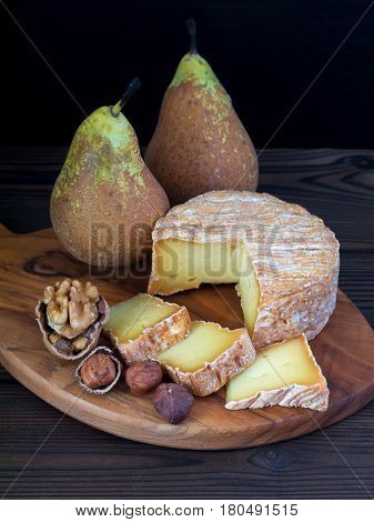 Soft washed-rind cheese walnut hazelnuts and pears on the wooden board