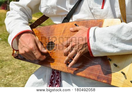Man plays an ancient traditional Russian musical instrument - gusli.