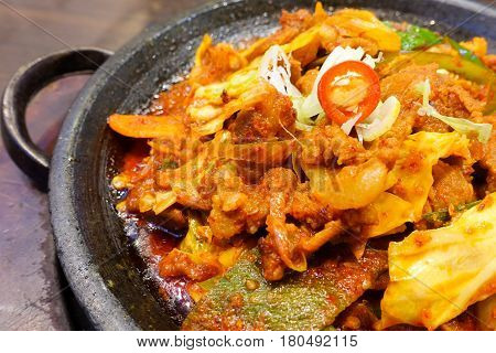 Korean spicy marinated pork with chillies and kimchi (Jae yook bok eum) serving on hot plate