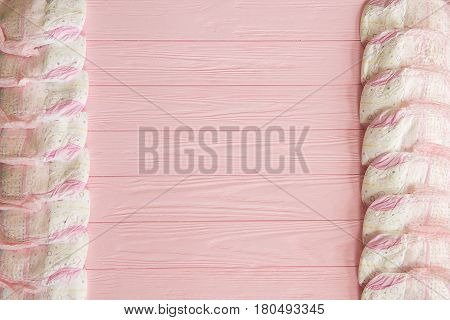 A newborn baby girl background. Pink diapers for a baby girl on a pink wooden background.