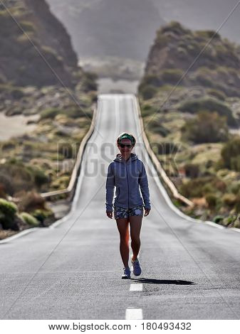 young Female Traveler walking on the road in Teide volcano crater, Tenerife, Spain