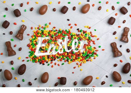 Chocolate easter eggs rabbits casks sweets colored candies and Easter lettering on concrete background. Horizontal orientation place for copyspace flatlay top view.
