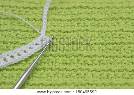 White crochet organic cotton chain pattern and steel hook on the green knitted background. Irish crochet lace craft bridal style