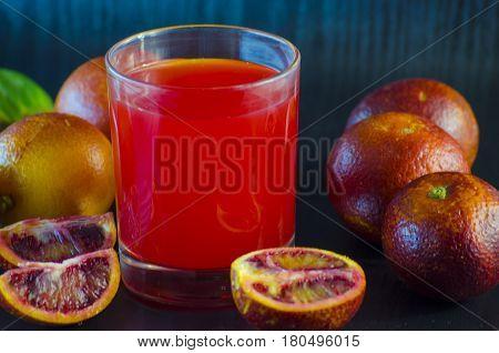 Juice of the Sicilian orange and fresh fruit on a black background
