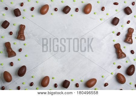 Chocolate easter eggs rabbits casks green sweet candies on concrete background. Horizontal orientation place for copyspace flatlay top view.