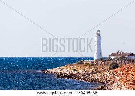 white lighthouse Hersones and road on the background of the sea in summer