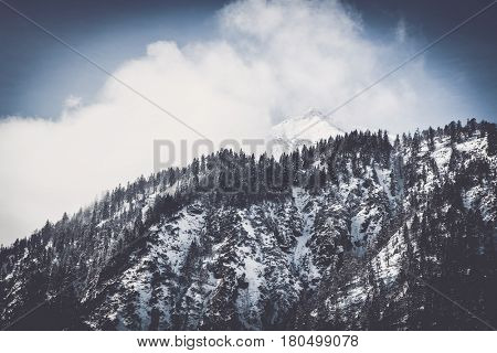 Snow-capped pinnacle alpine summit with low lying cloud cover obscuring the peak in a cold winter landscape with evergreen forests