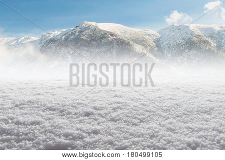 Winter snow ice Background with snowflakes and blurred mountains far behind