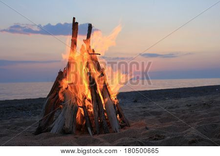 Bonfire on the beach on sunset background