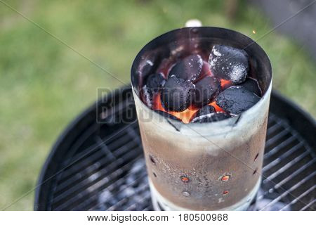 BBQ Grill Pit With Glowing And Flaming Hot Charcoal Briquettes coal Food Background Or Texture Close-Up Top View