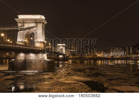 Chain Bridge at nighttime with icy Danube and city