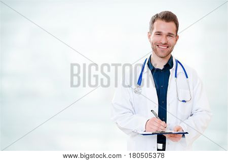 Handsome Young Smiling Doctor With Clipboard