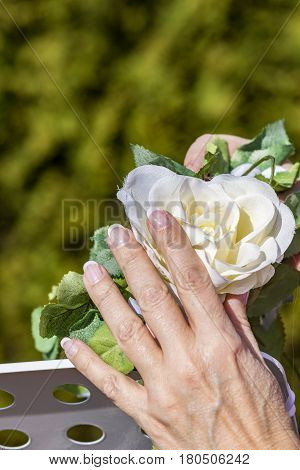 woman prepares the flowers at the wedding gate under blue sky