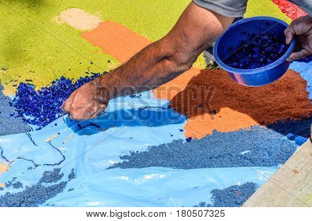 Antigua, Guatemala - March 26 2017: Local decorates Lent carpet with dyed sawdust in colonial town with most famous Holy Week celebrations in Latin America.
