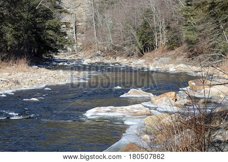 Icy Loyalsock creek flowing through the boulders and around the bend.