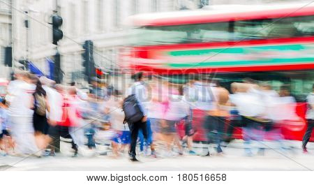 London, UK - August 24, 2016: Piccadilly circus with lots of people, tourists and Londoners crossing the junction. Red bus at the background. Blurred type image