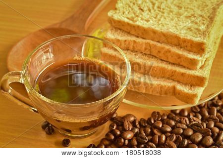 Coffee cup with whole wheat bread and scattered roasted coffee beans on Wooden Table