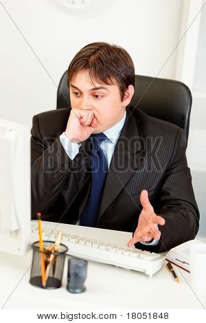 Confused business man sitting at office desk and surprisingly looking at computer monitor