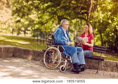 Young carer woman reading book outdoor disabled senior man in wheelchair