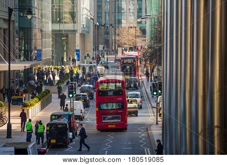London, UK - March 15, 2017: Canary Wharf street view with lols of walking business people and transport on the road. Business and modern life of London