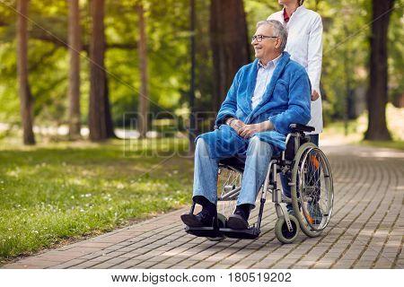 portrait of elderly man on wheelchair with nurse outdoor