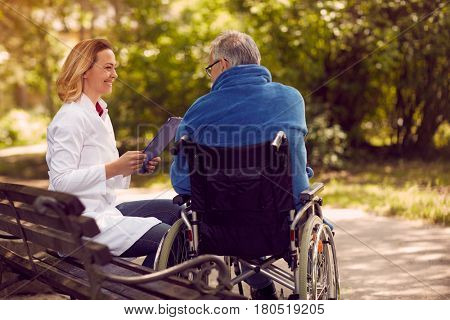 Hospice nurse checking up the history of the patient in wheelchair