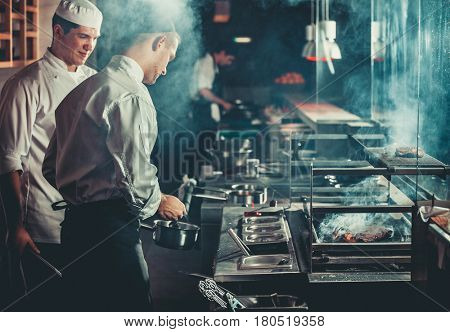Food concept. Chef in white uniform monitors the degree of roasting and greases meat with oil in saucepan in interior of modern restaurant kitchen. Preparing traditional beef steak on barbecue oven.