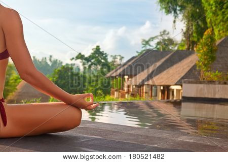 Good morning with yoga meditating on sunrise background. Active woman in bikini practicing on villa poolside to keep fit and health. Woman fitness training sport activity on summer family holiday.