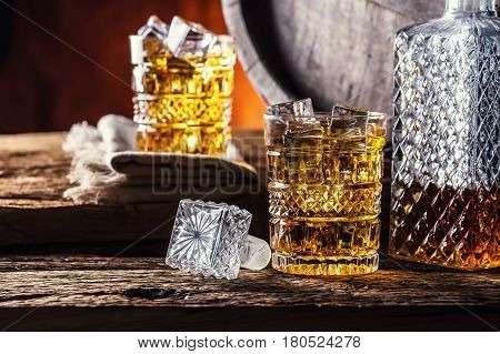 Whiskey. Two cups full of beverage whiskey brandy or cognac with ice cubes in retro style. Old oak barrel in the background.