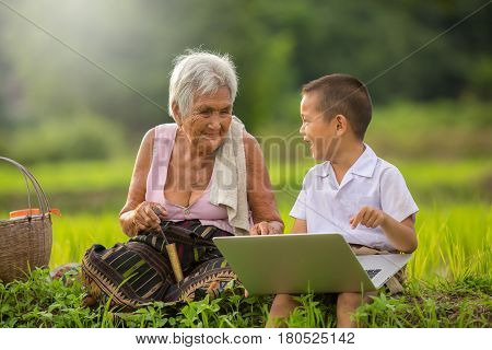 Asian grandmother with grandchildren play computer in farm