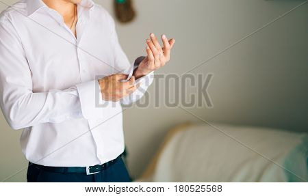 Buttoning cuffs. The groom wears cufflinks. Businessman inserts shirt cuffs.