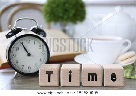 Retro alarm clock showing five minutes to eleven and wooden cubes with word TIME on lunch table
