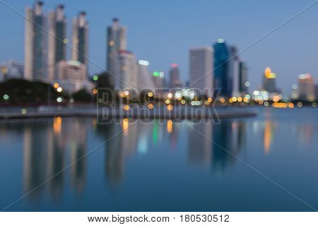 Reflection blurred bokeh light Office building water front at twilight abstract background