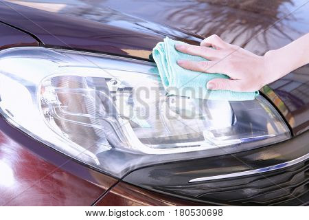 Female hand with rag cleaning car headlight