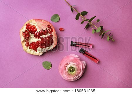 Beautiful composition with perfume samples,  pomegranate and flower on color background
