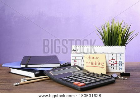 Paper sheet with text TAX DEADLINE, calculator and notebooks on wooden table