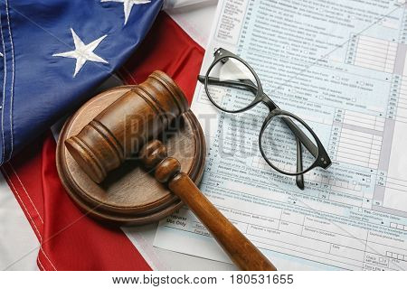 Judge gavel, eyeglasses and tax form on American flag background