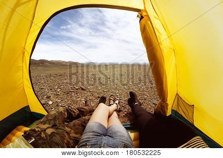 Group of three friends having rest in yellow tent. Photo of legs in tents door from first view