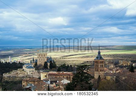 Castle Of Segovia, A Tower And Old Medieval Buildings With Fields At The Baackground, A View From An