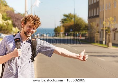 Young man hitchhiking on summer vacation. Happy guy tourist beside road with thumb up gesture having fun.