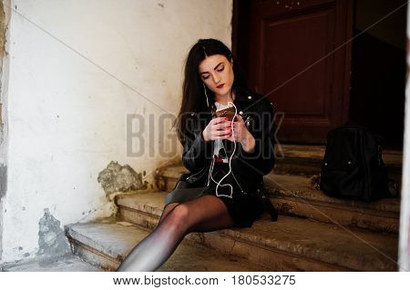 Young Goth Girl On Black Leather Skirt And Jacket Sitting On Stairs Of Old House, Listening Rock Mus