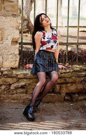 Young Goth Girl On Black Leather Skirt And High Heels Punk Shoes Posed Against Iron Fence.