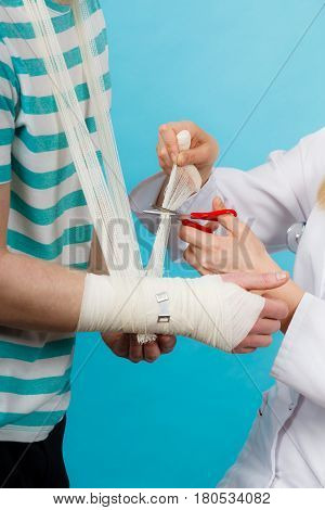 Medicine and healthcare. Female doctor bandaging male hand sprained wrist. Young man visiting medical professionalist.