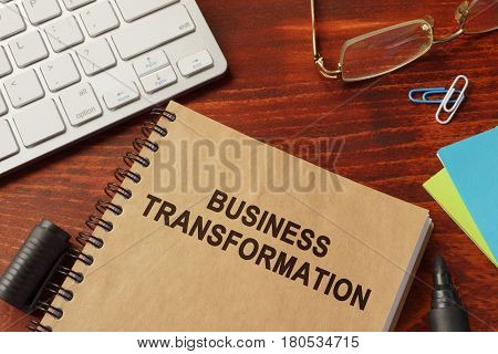 Book with title business transformation in an office.